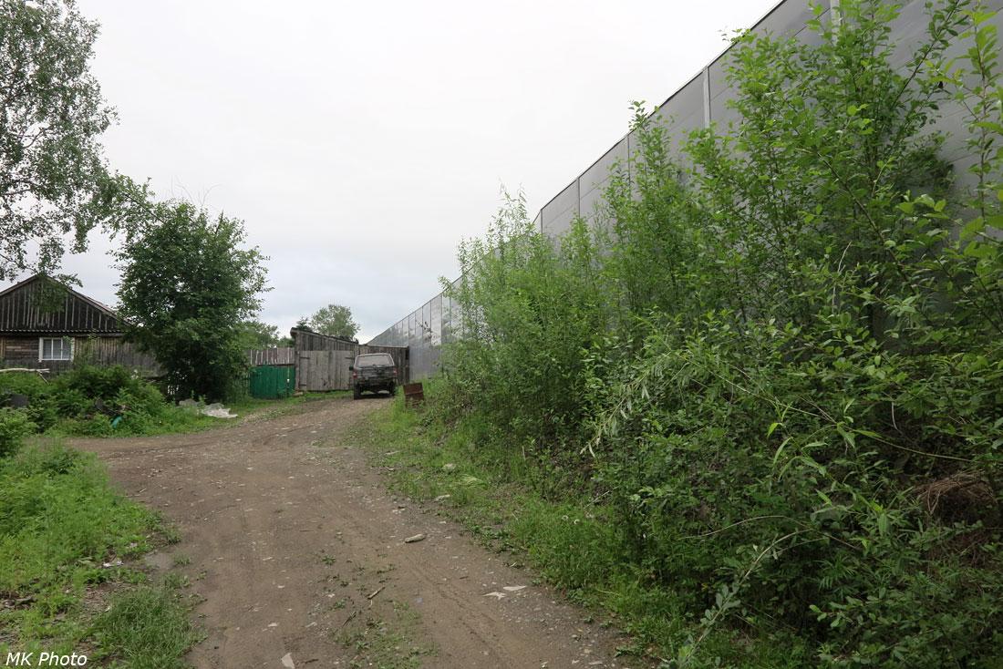 Шумозащитный забор между посёлком и станцией Тулучи